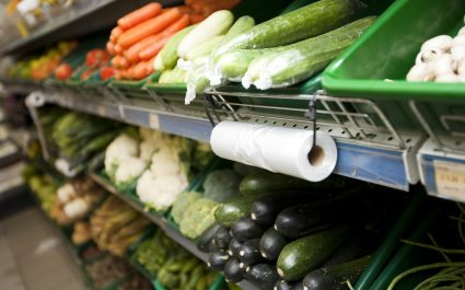 Supermarket vegetable section with close-up of plastic bag roll - Plus Pack