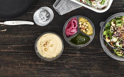 DeliWave™ food packaging clear PET tray on table with houmous hummus and dip next to salad in round salad bowl