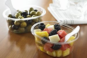 Clear oval trays with fruit salad and with olives with small plastic spork - Plus Pack